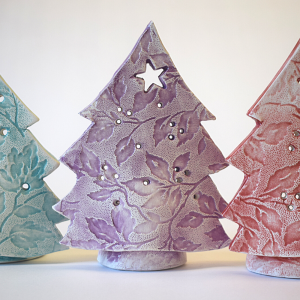 Purple ceramic tree with a cut out star the top tealight holder, on a white background.