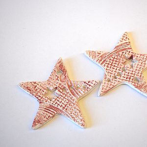 Two red ceramic star decorations on a white background