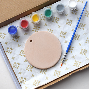 Round ceramic object, with 6 paint pots, colours blue, red, yellow, green, silver and white. Plus a paint brush. Presented in a box.
