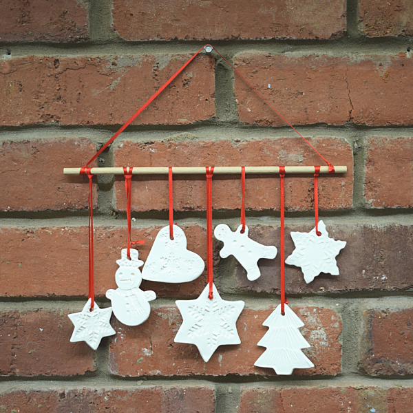 Ceramic mobile. 7 festive shapes on red ribbon hanging from a wooden dowel, against a brick backdrop.