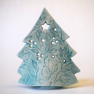 Blue ceramic tree with a cut out star the top tealight holder, on a white background.