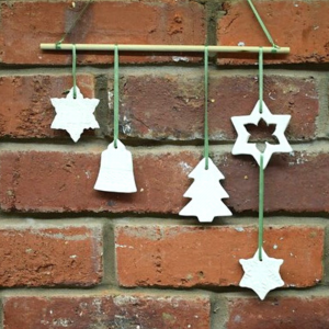 Ceramic mobile. 5 festive shapes on green ribbon hanging from a wooden dowel, against a brick backdrop.
