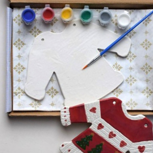 Ceramic Christmas jumper craft pack. With one paint brush and 6 paints; blue, red, yellow, green, silver and white. Presented in a box. Complete with an example of a finished design.