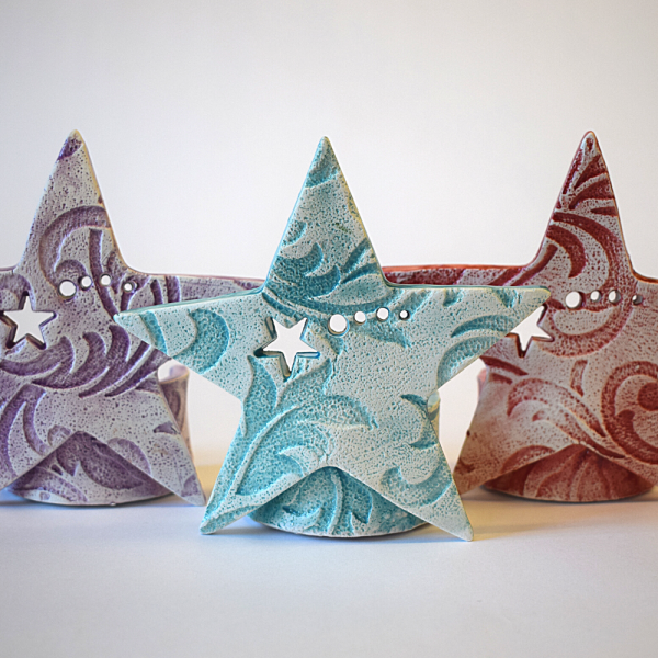 3 ceramic star tea light holders in purple, blue and red