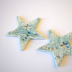 Two blue ceramic star decorations on a white background